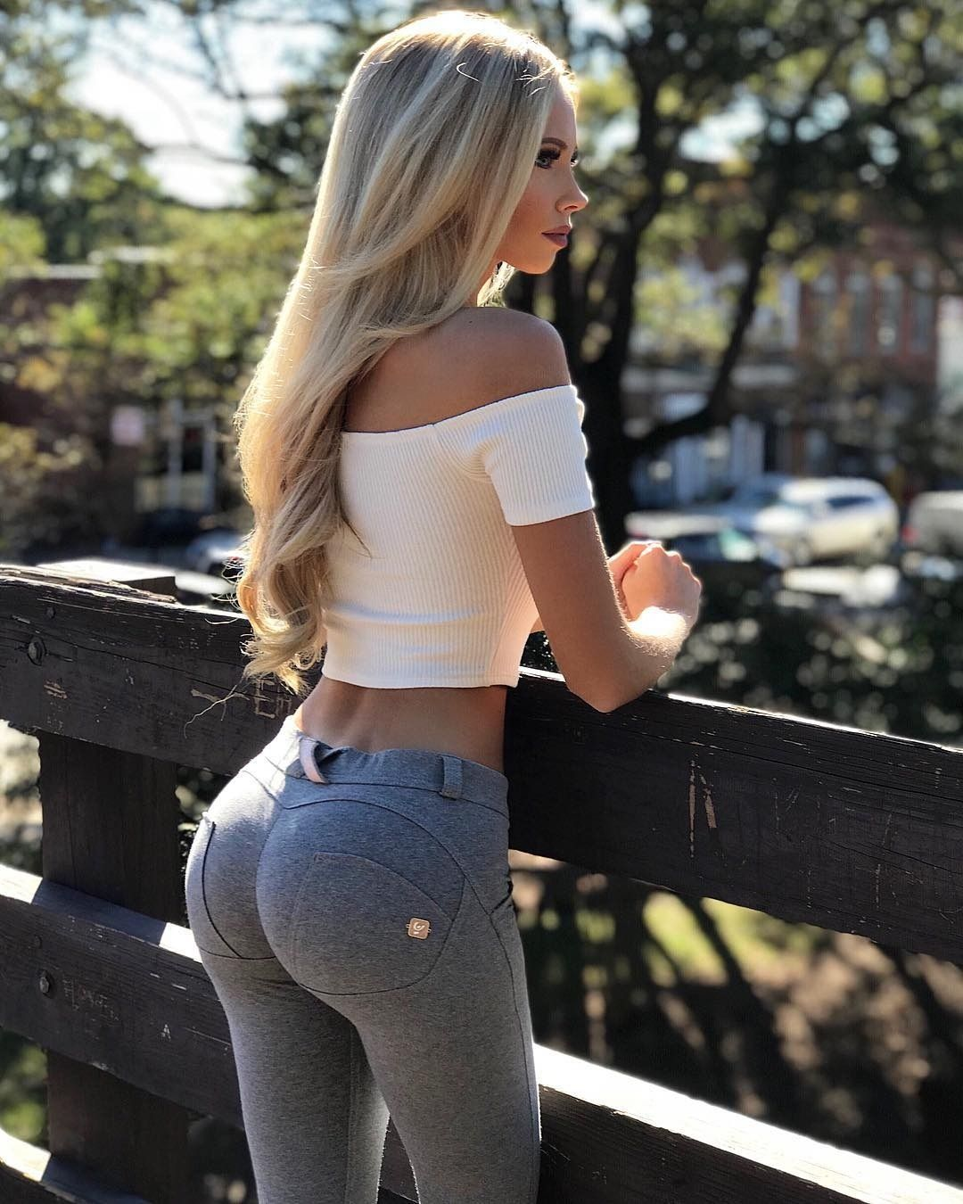 Blond Woman In White T Shirt Trying To Dress Her Tight Jeans Stock Image