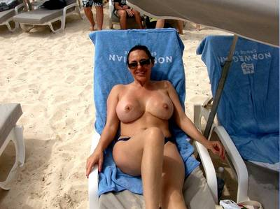 Busty MILF relaxing at the topless beach