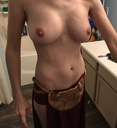 Skinny and busty in half of her Princess Leia slave girl outfit.